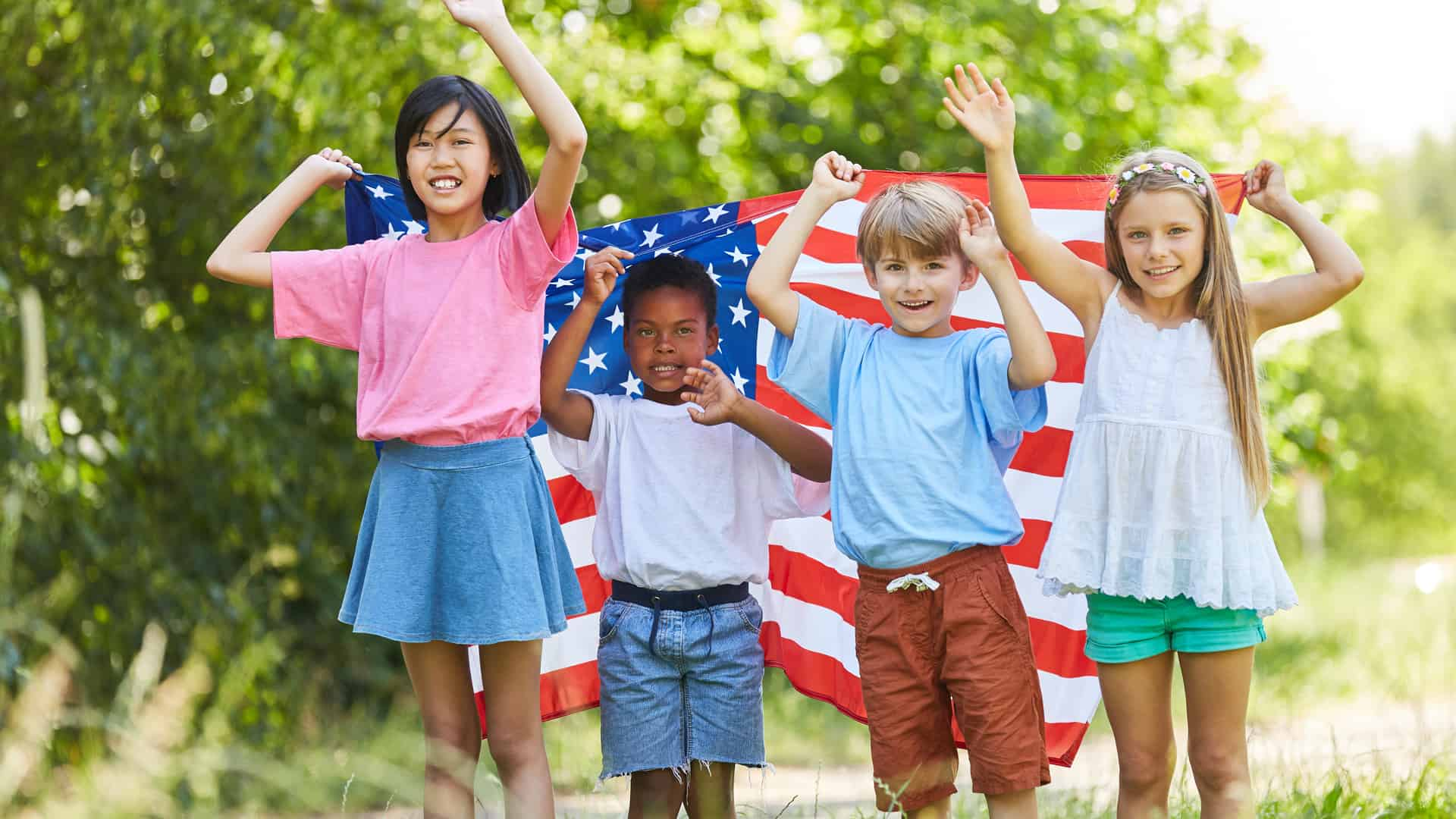 Multicultural group of kids waving with US flag on Labor Day