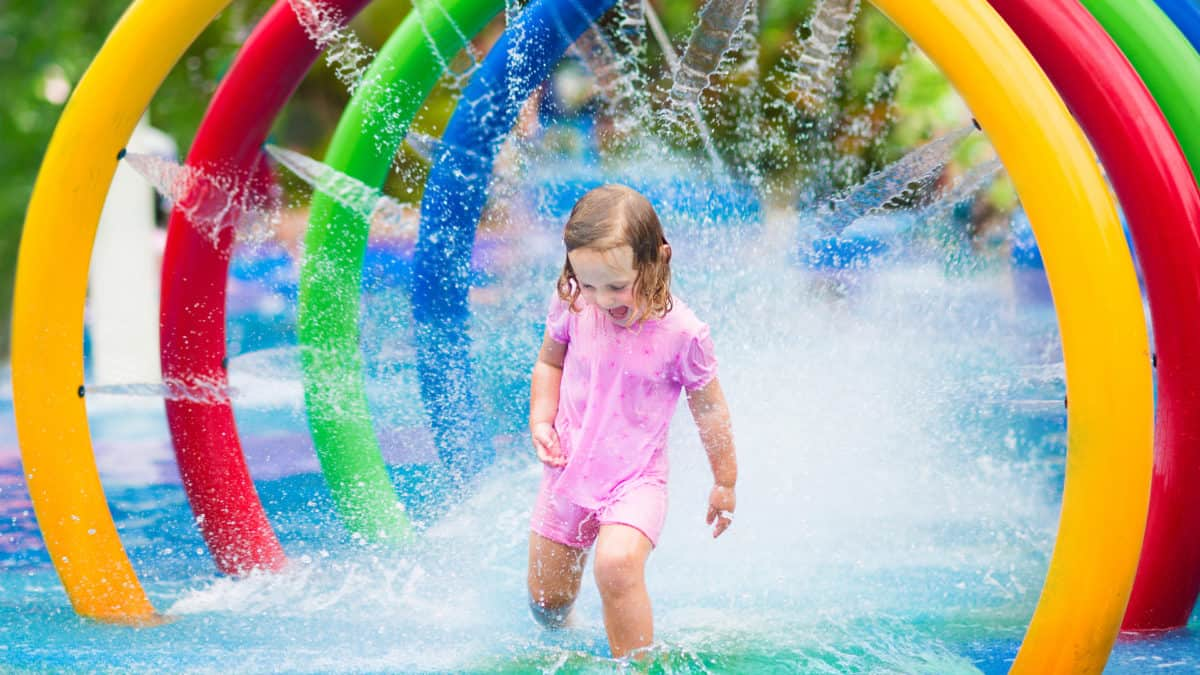 Happy toddler girl running through a water fountain in a swimming pool enjoying water amusement park while on summer vacation