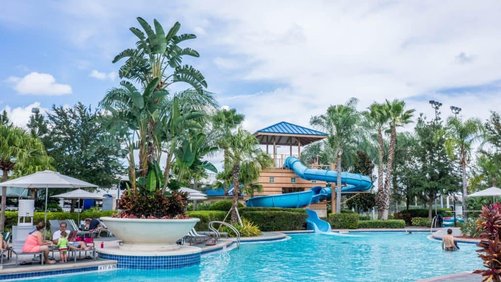 Family sitting near pool in waterpark with slides in USA