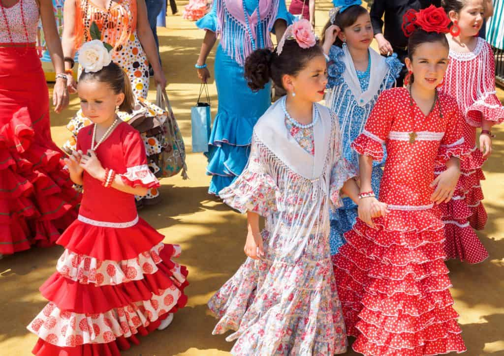 Spanish girls in traditional dress walking alongside Casitas at the Seville Fair called Feria de Abril
