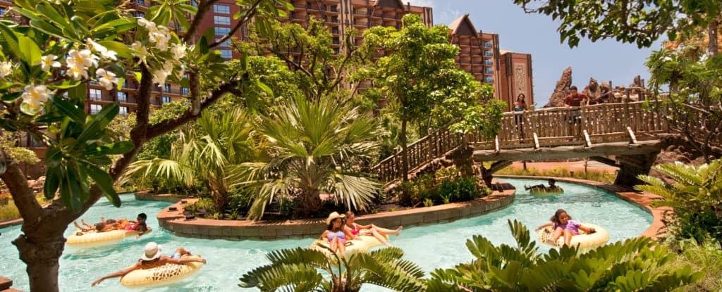 Girls having fun at lazy river swimming pool with trees at Aulani Disney Waikolohe Valley Resort
