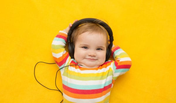 Baby equipped with headphones on a yellow background