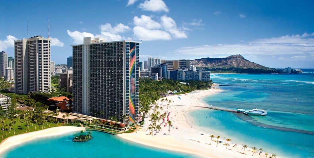 Aerial view of ocean beach with Hilton Hawaiian Village Waikiki Beach Resort in the background