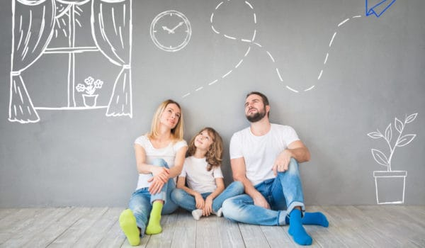 Happy family of trusted house sitters, sitting on wooden floor. Interior design concept on walls