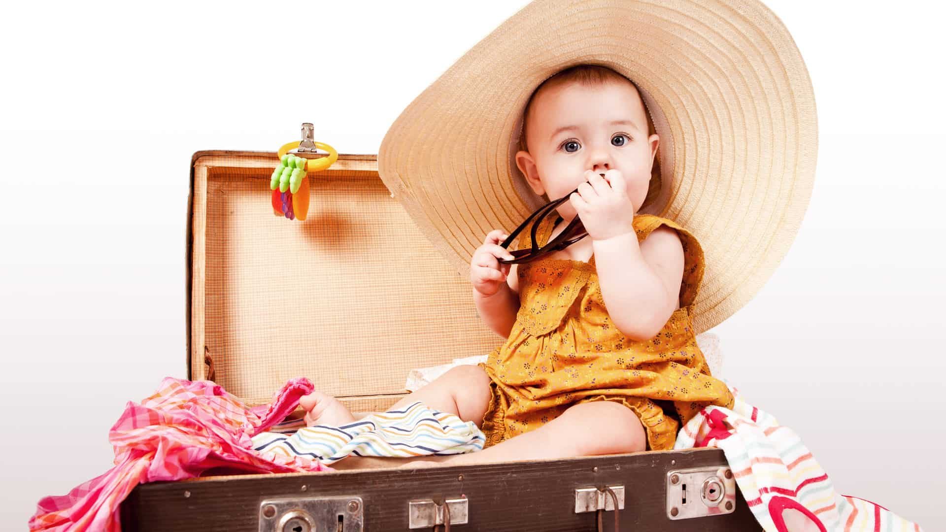 Cute baby with big summer sombrero sitting in an old suitcase ready to travel