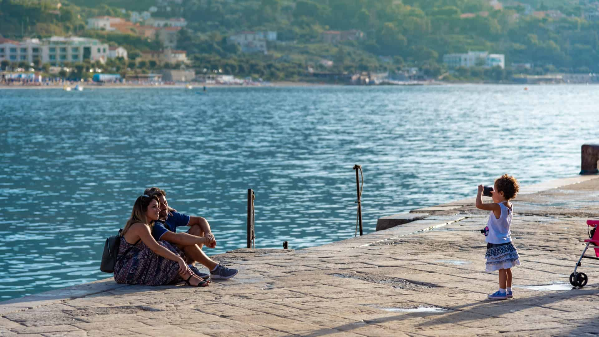 Happy and cute family in Cefalu Sicily, little girl taking picture