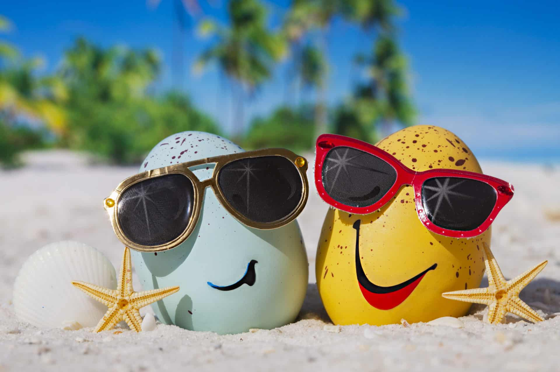 Two Easter eggs wearing sunglasses on a beach