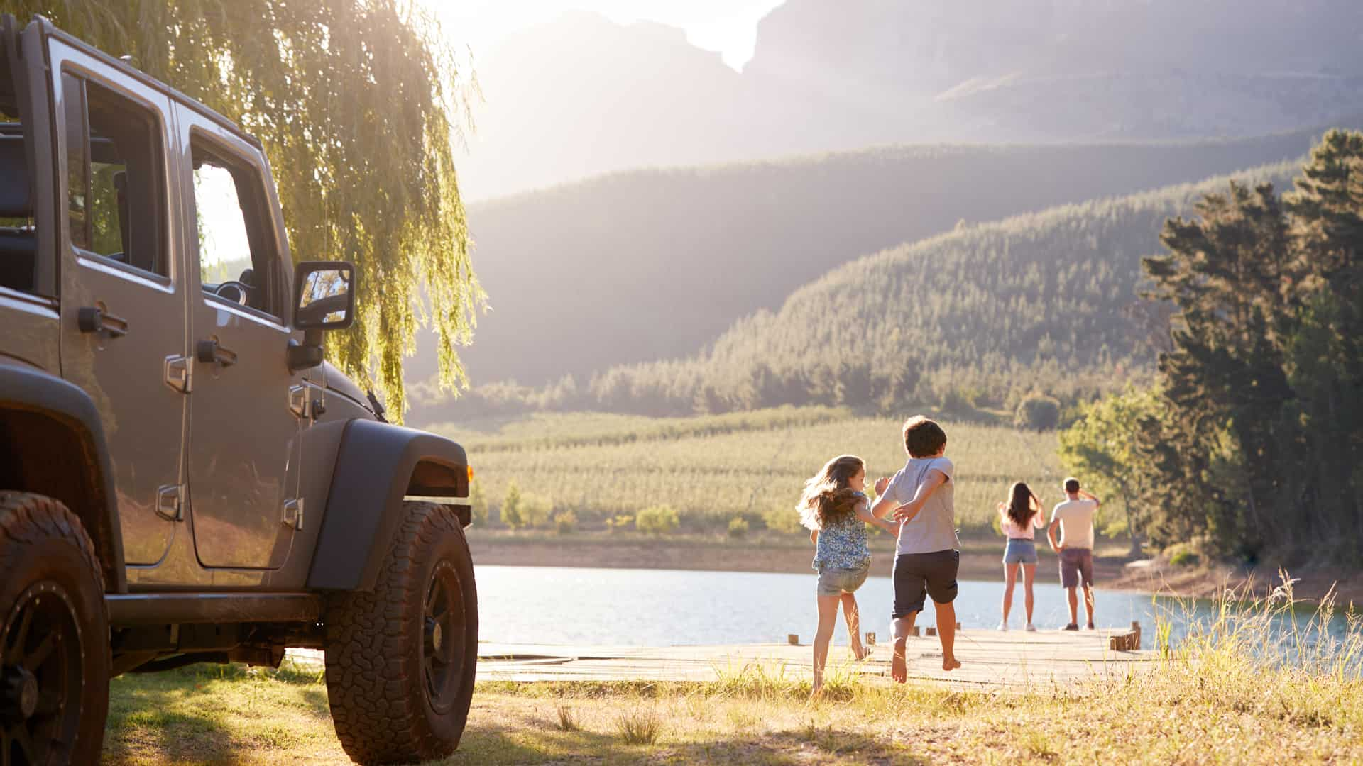 Happy family on road trip reaching lake in the countryside with mountains in the background