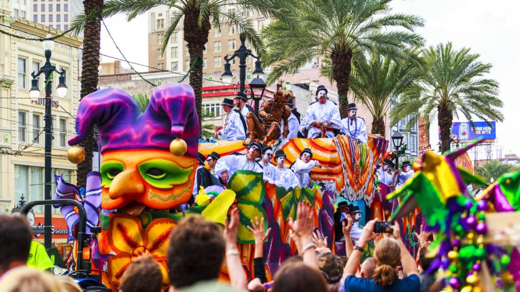 Mardi Gras parades through the streets of New Orleans with people cheering