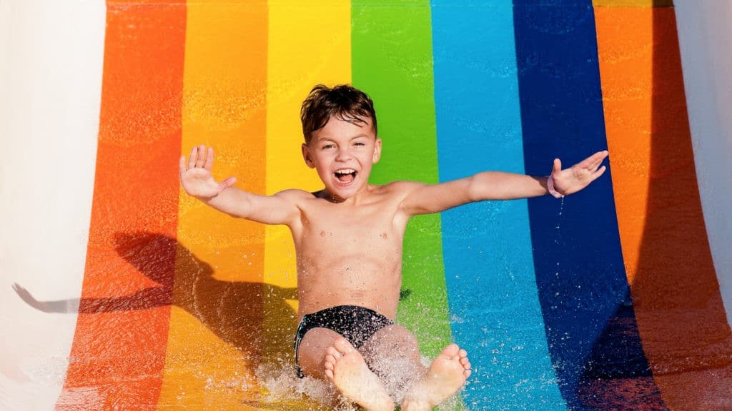Boy having fun while sliding down a water slide in a water park