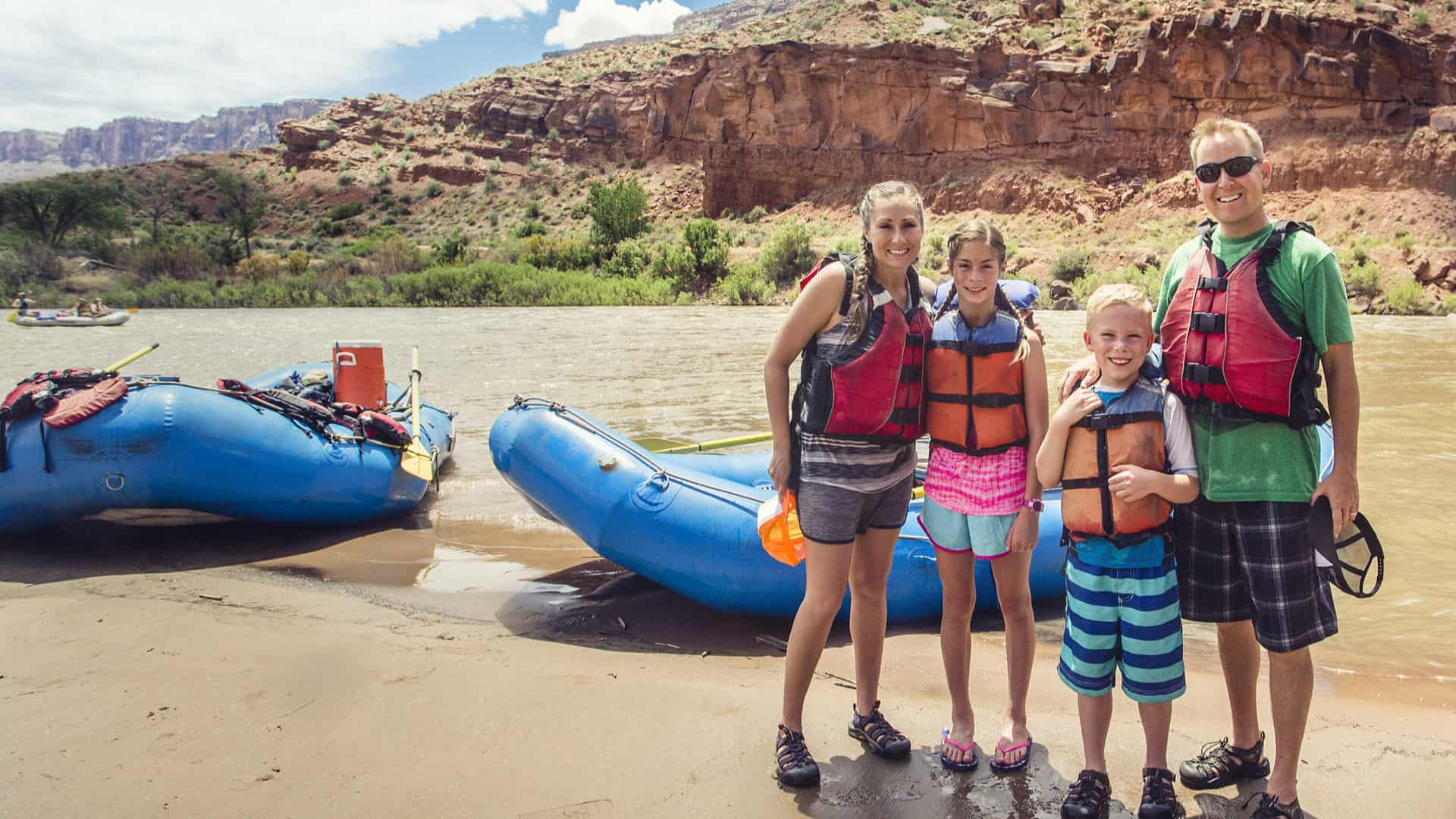 Family rafting on the Colorado River in Arizona with boats, river, and mountains in the background
