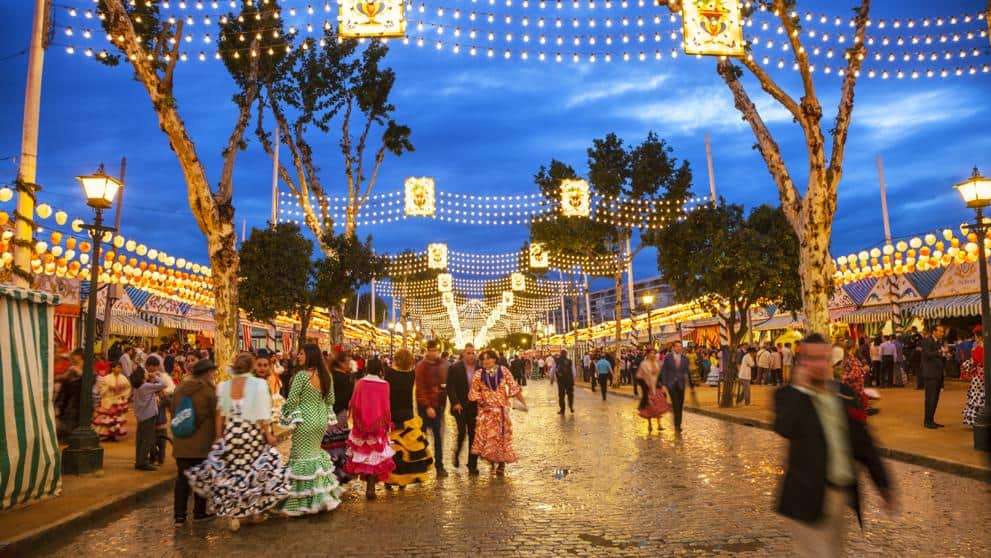 Night scene at the Feria de abril de Sevilla, the Seville Fair with casetas, tents in the background and people in traditional dresses