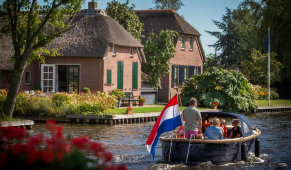 Family taking a boat trip in Giethoorn, Holland, the Netherlands, with typical houses in the background