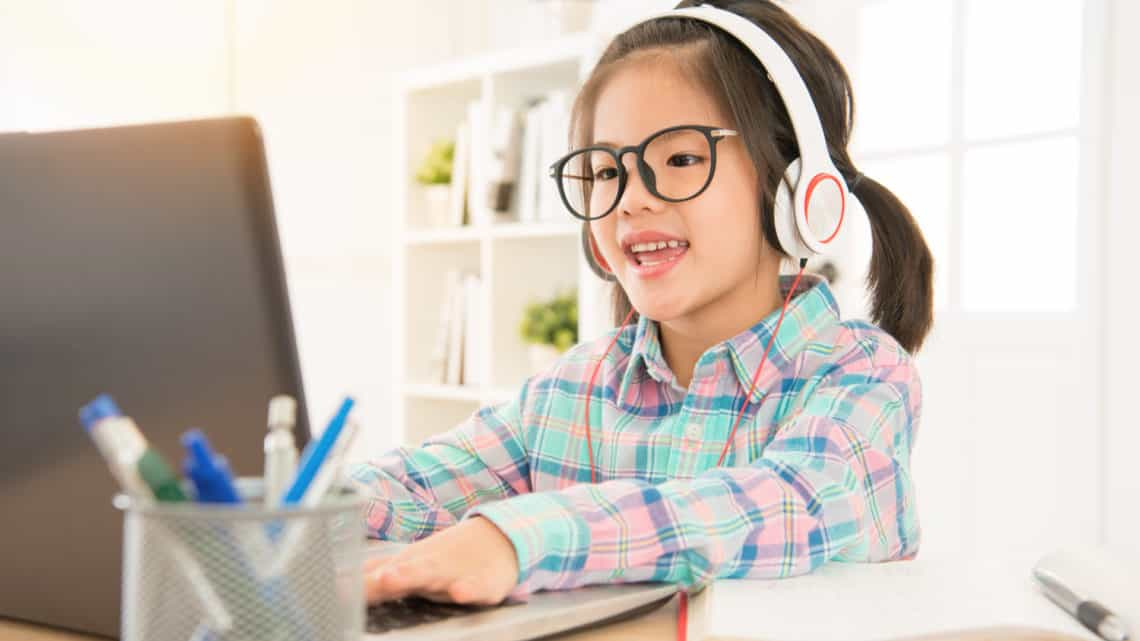 Girl with Asian roots sitting in front of a computer doing elearning and online classes using headsets