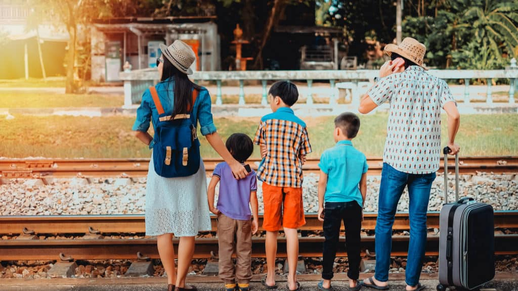 Family with three children waiting for a train right next to the tracks