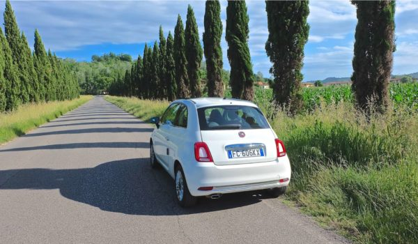 White Fiat 500 on a road trip in Tuscany Italy with typical landscape