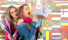 Two girls shouting by megaphone about learning new languages with flags in background