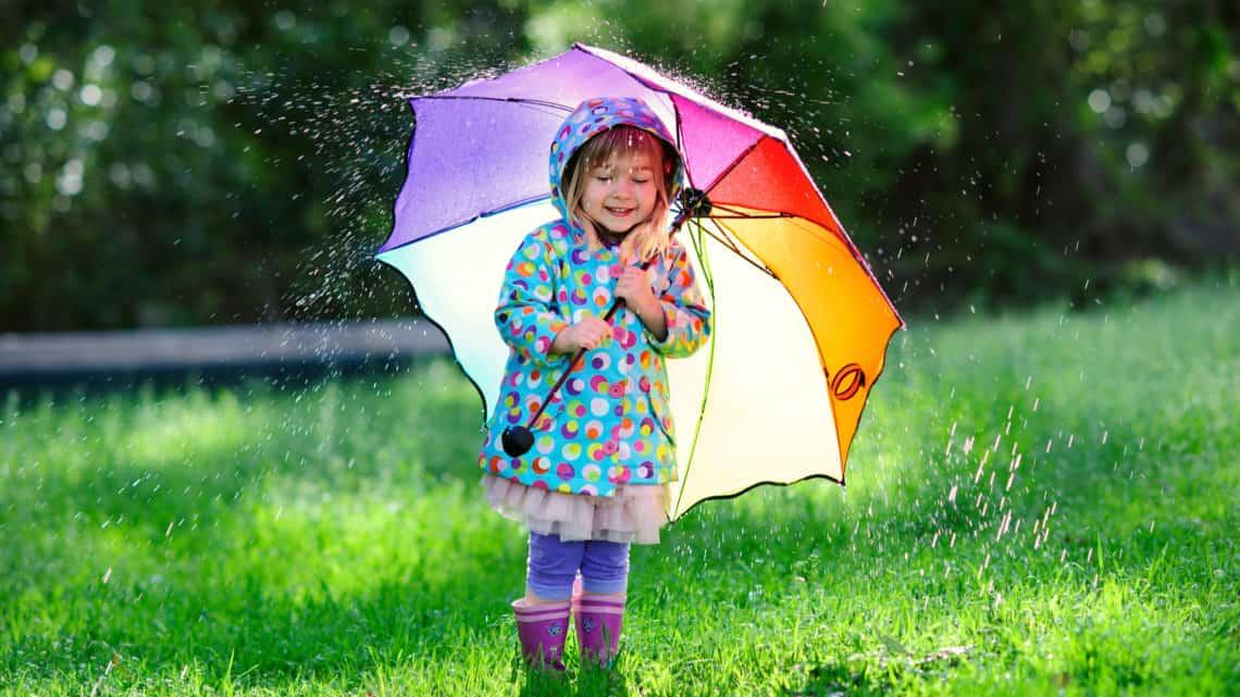 Cute girl standing in the rain under an umbrella in the grass
