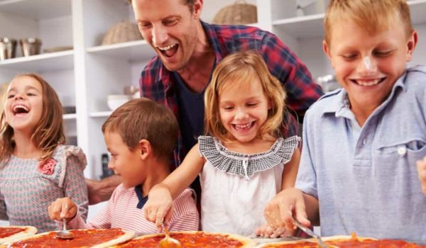 Father cooking pizza with happy kids in a kitchen