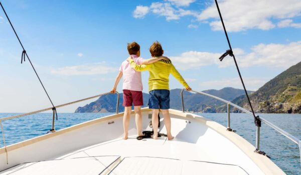 Two boys standing on deck of a sailing boat looking towards the coast in Croatia