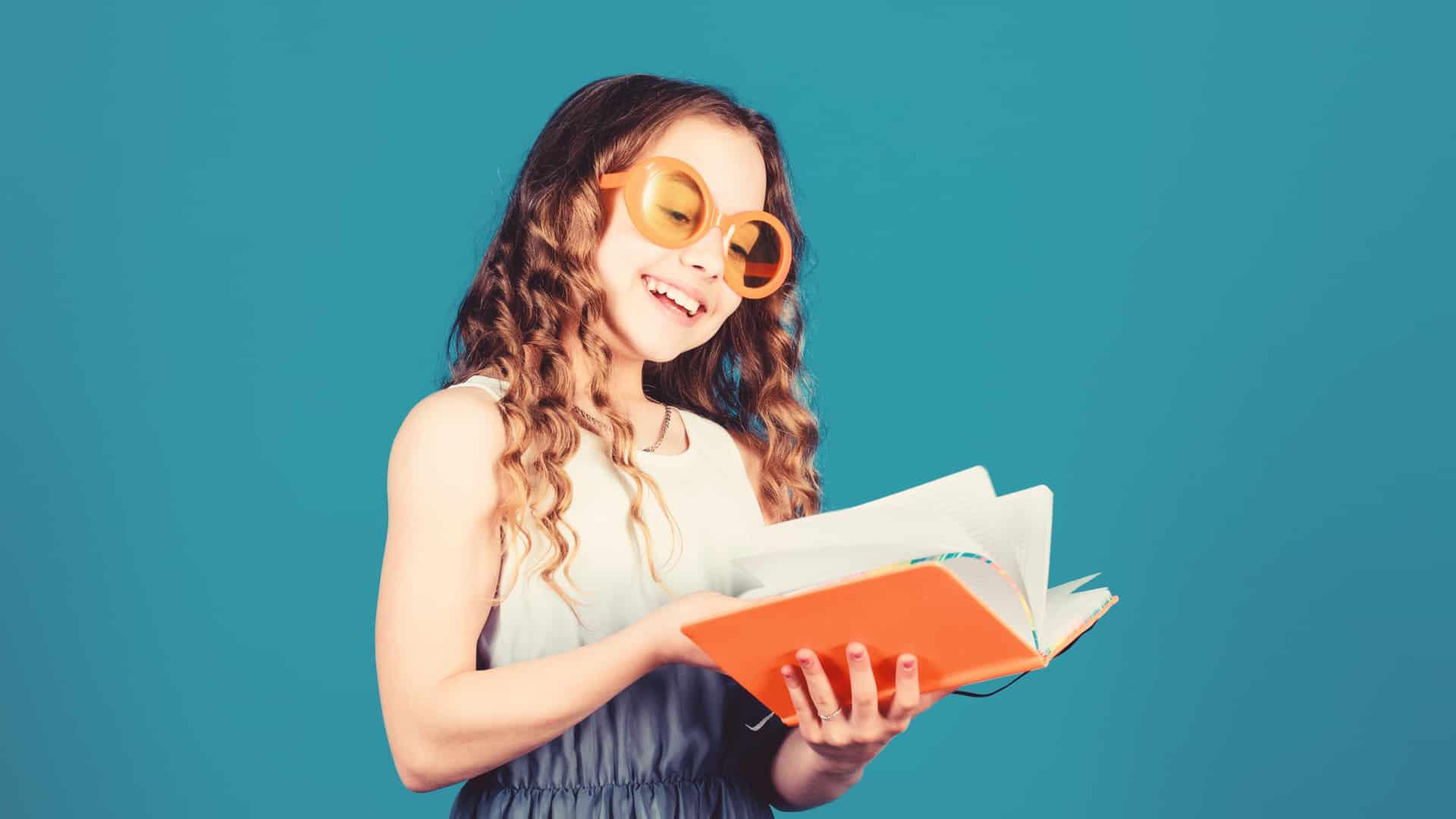 Happy kids reading an orange summer book