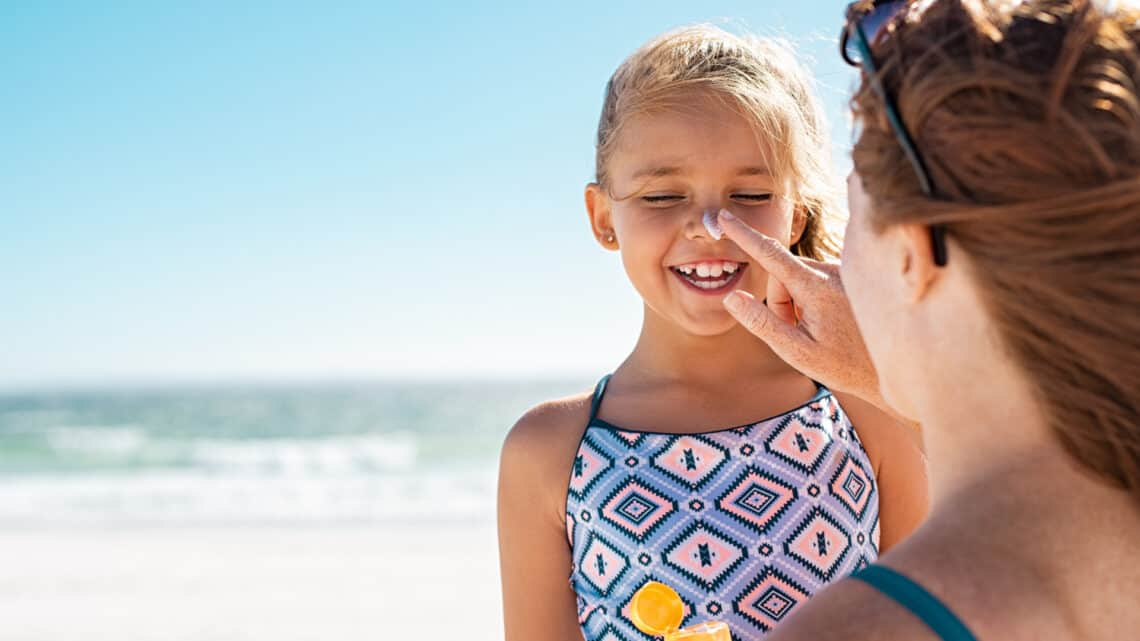 Mother applies sunscreen on her daughter's nose and face