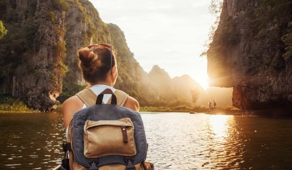Girl with a carry-on backpack enjoying sunset in Halong Bay in Vietnam