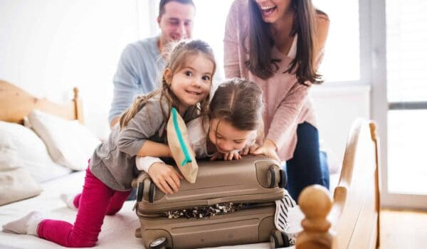 Parents with two kids over a suitcase getting them ready for a trip abroad