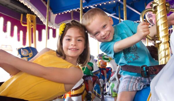 A boy and a girl having fun in a carousel at an amusement park carnival in Europe