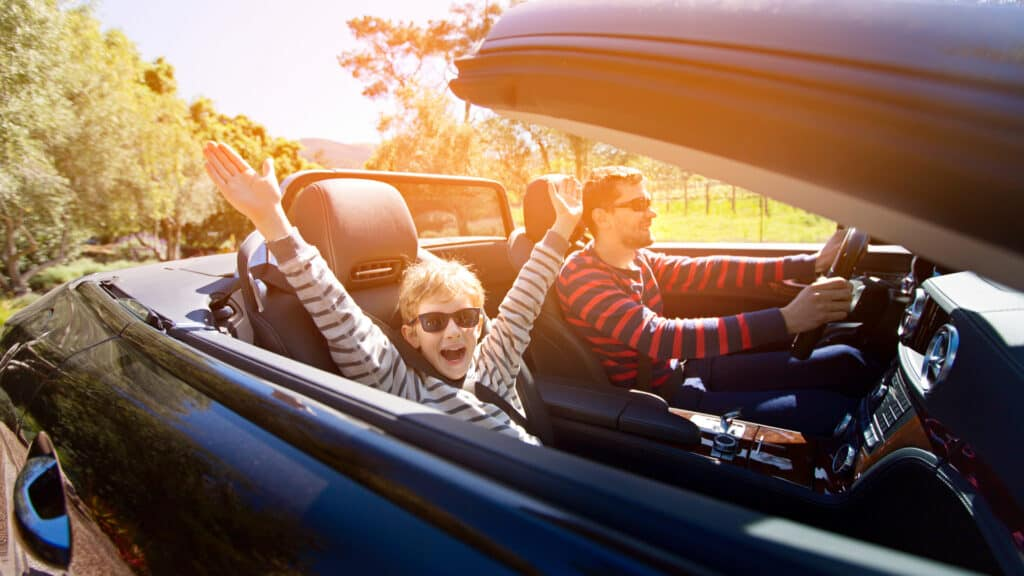 Father and son on a road trip in a convertible car in California, USA