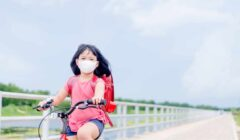 Asian girl riding a bicycle with a mask in a post COVID-19 world