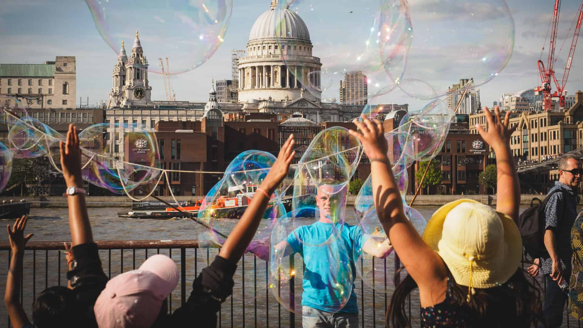 Happy kids having fun with soap bubbles on South Bank of the Thames river, with St. Paul's Cathedral in London, U.K.