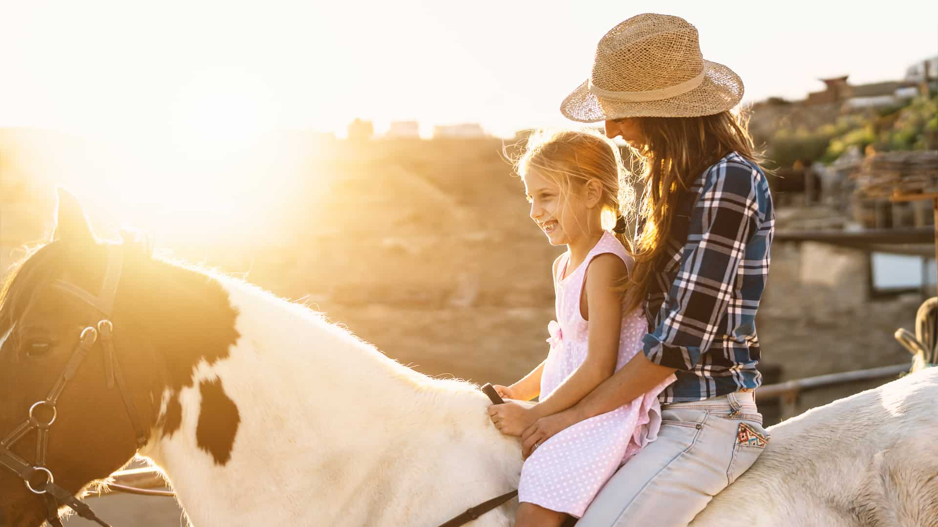 Happy family with mother and daughter on a horse on a farm in Texas, USA