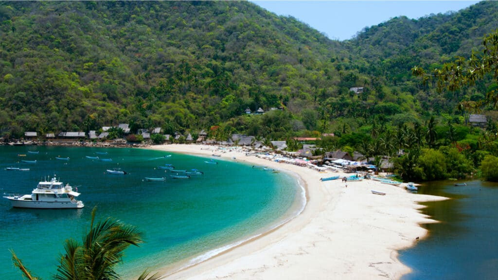 Hidden tropical beach in Mexico with a boat and hills in the background