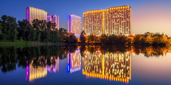 Hotel Izmailovo with four towers in Moscow, Russia at night with lake