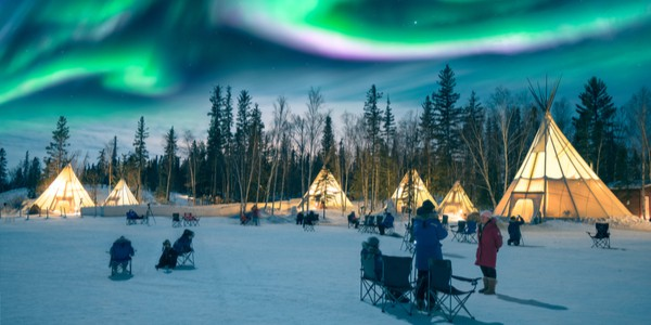 Northern lights dancing over the tepees at Aurora Village in Yellowknife, Canada