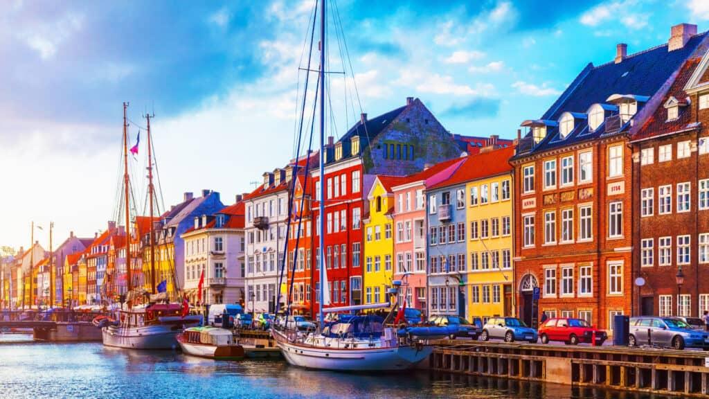 Summer sunset at Nyhavn pier in Copenhagen, Denmark with boats